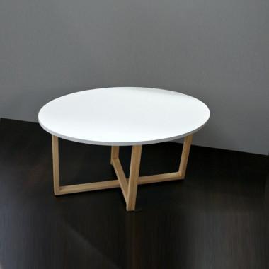 Stolik kawowy WOMEB OVALDES2 z białym owalnym blatem i drewnianymi nogami w kształcie krzyżujących się ramek.