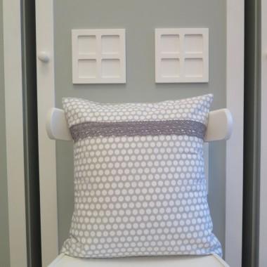 Szara poduszka w białe grochy z koronką.
