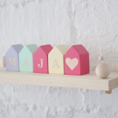 Klocki drewniane w kształcie domków z literami.