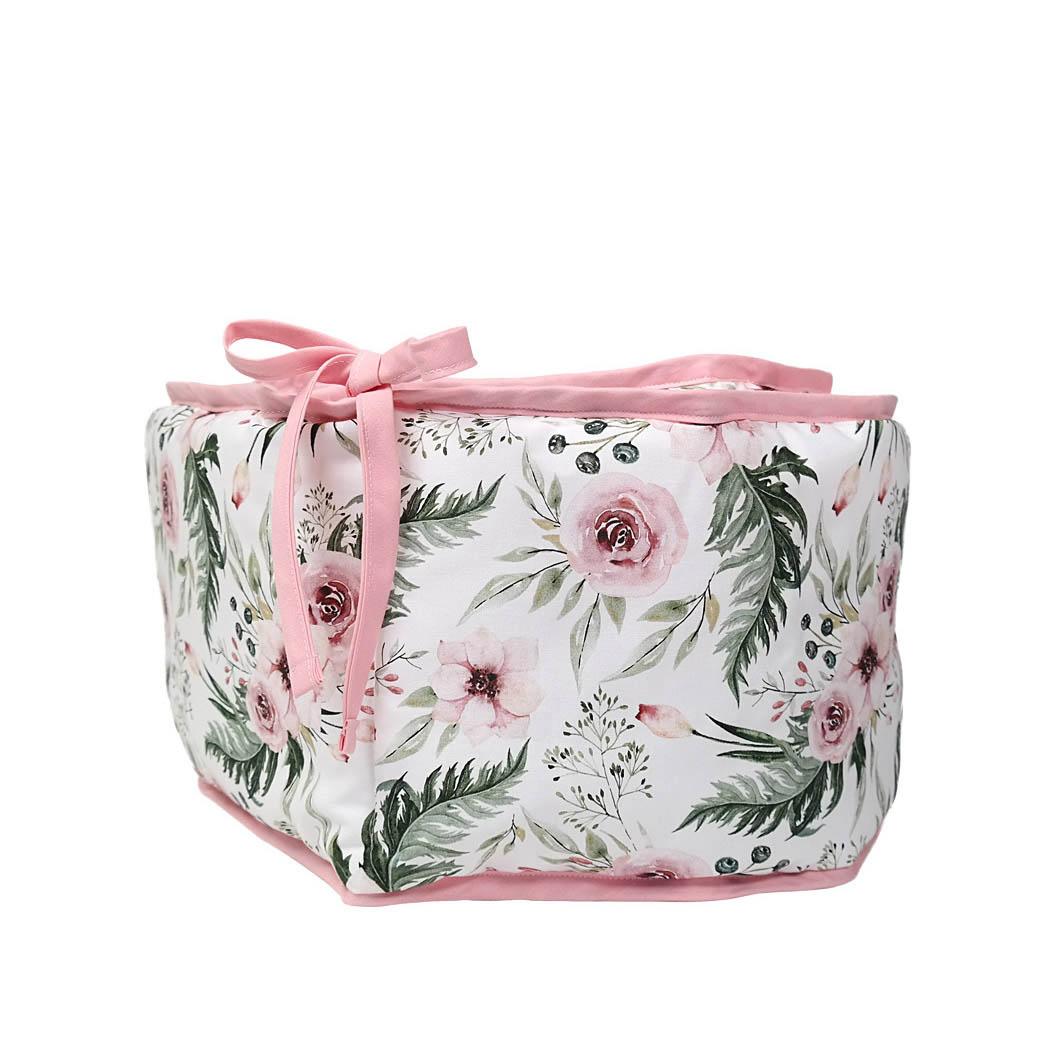 Ochraniacz do łóżeczka pikowany z zewnętrznej strony, od wewnątrz wykonany z tkaniny z nadrukiem w kwiaty.