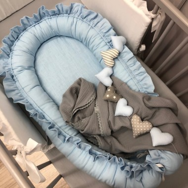 Kokon niemowlęcy doskonale otula maleństwo do snu. Gniazdko zostało uszyte z błękitnej, lnianej tkaniny.