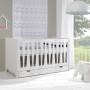 Białe łóżeczko niemowlęce z regulowaną wysokością.
