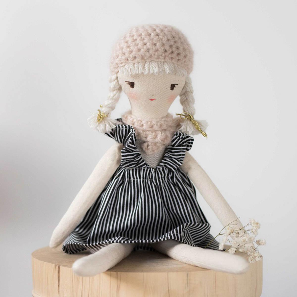 Lalka Maia ubrana w lniane body w kolorze beżowym, spódniczkę bawełnianą w czarno białe paski oraz szalik i beret w kolorze beżowym.