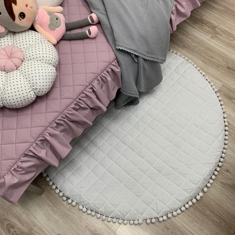 Biała mata dla niemowlaka z szarymi pomponikami. Idealna do leżeniu lub zamiast dywanika do zabawy. Dekoracja do pokoju dziecka.