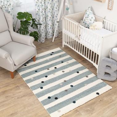 Biało - niebieski dywan w paski i kolorowe kropki.