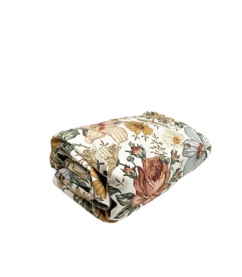 Prześcieradło dla dziecka wykonane z wysokiej jakości tkaniny w kwiaty, zakładane na gumkę.